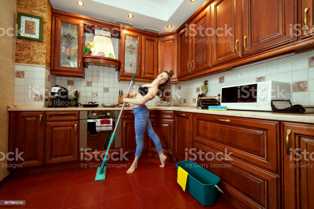 Woman washes the floor with a mop. stock photo