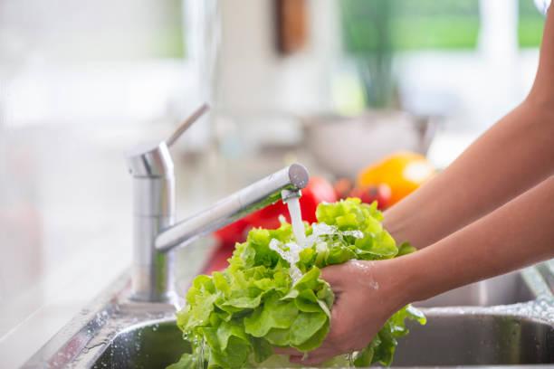 Frau Waschen hellgrünen Salat im Waschbecken – Foto