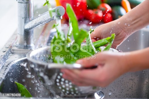 Woman Washing  bright green snow peas in a colander in the sink. Running water over the vegetables with splashing droplets. Close up with action and motion.