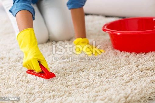 istock Woman washing carpet with brush 495798962