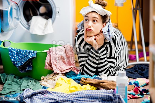 Unhappy housewife sitting with socks near the washing machine with colorful clothes on the floor at home