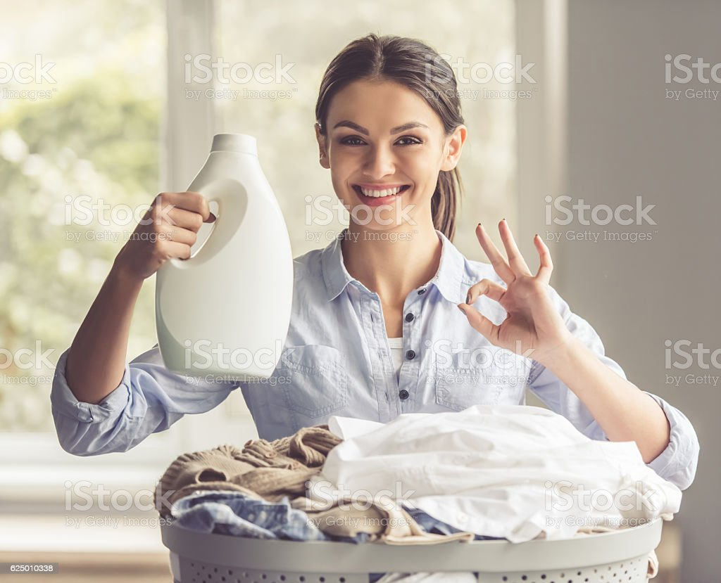 Woman washing clothes Beautiful young woman is holding a fabric softener over the basin with laundry, showing Ok sign, looking at camera and smiling Adult Stock Photo