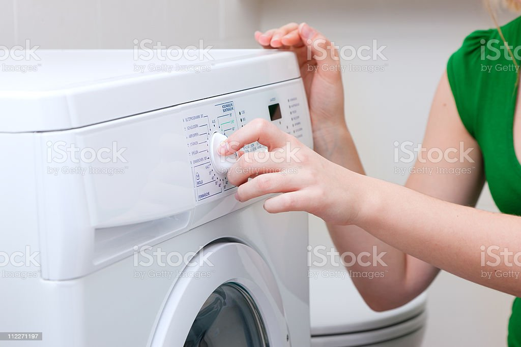 Woman washing clothes with machine stock photo