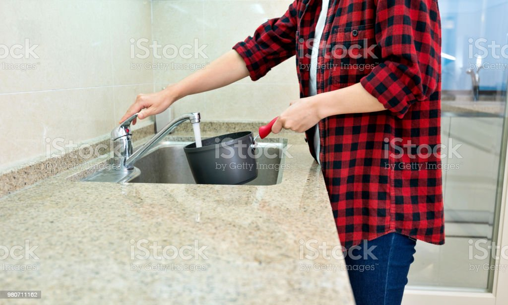 Woman washing cooking pot in kitchen.