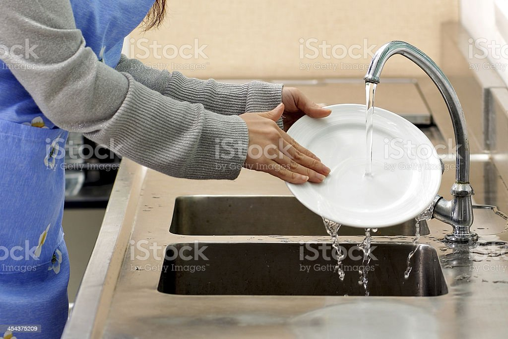 Woman washing dish in sink stock photo