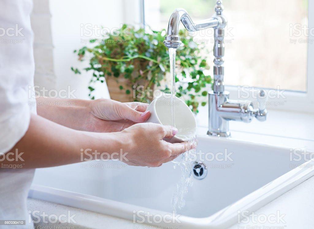 Woman washing dish in sink foto