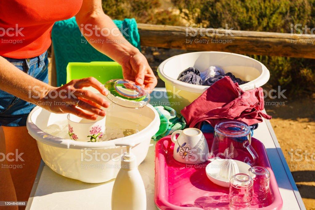 Frau Waschen Geschirr In Schussel Kaptern Im Freien Stockfoto Und Mehr Bilder Von Abwaschen Istock