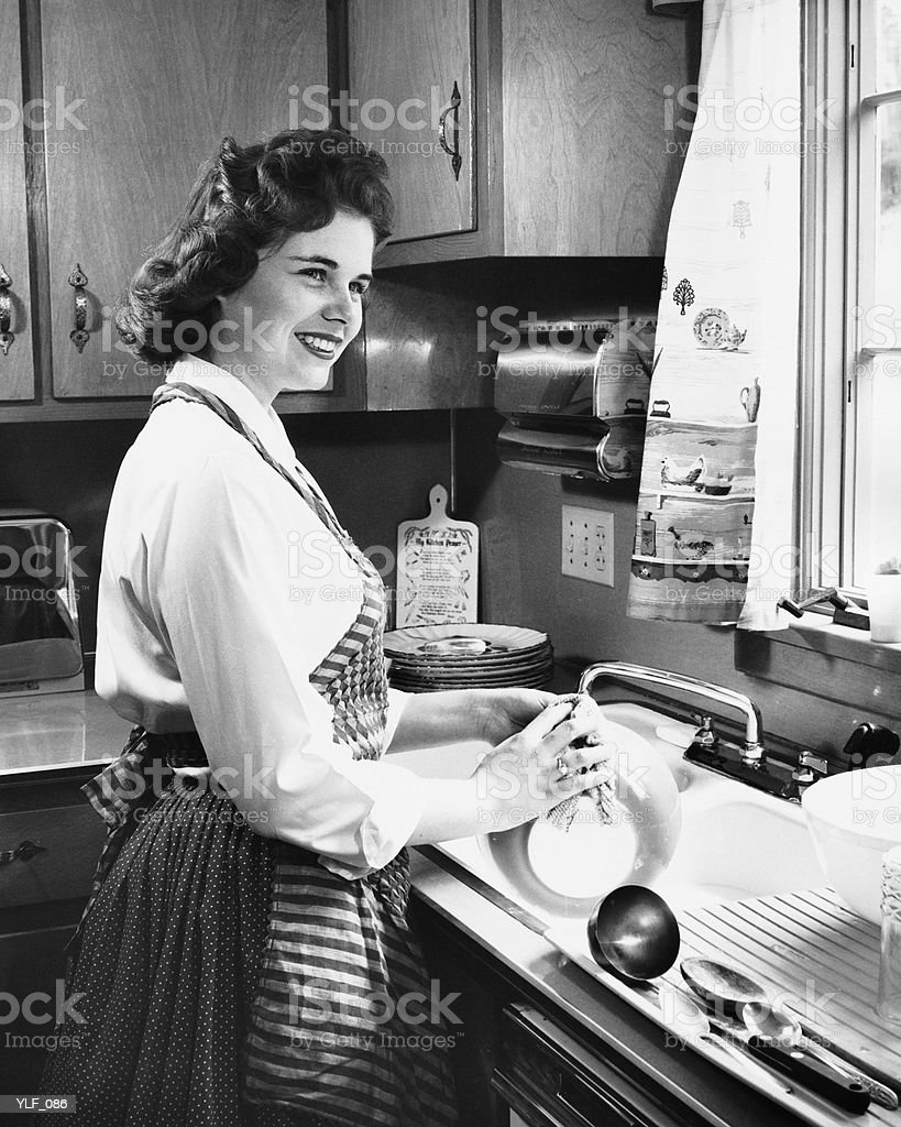 Woman washing dishes in kitchen royalty-free stock photo