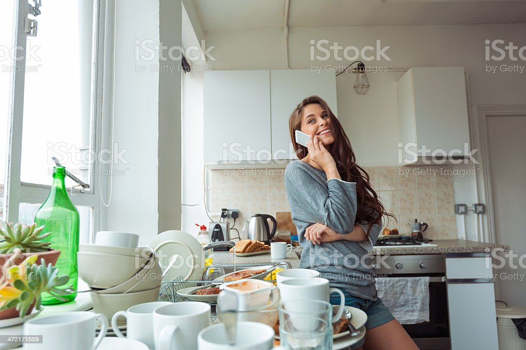 Woman washing dishes Young woman going to cleaning kitchen, standing next to sink and talking on phone. 20-24 Years Stock Photo