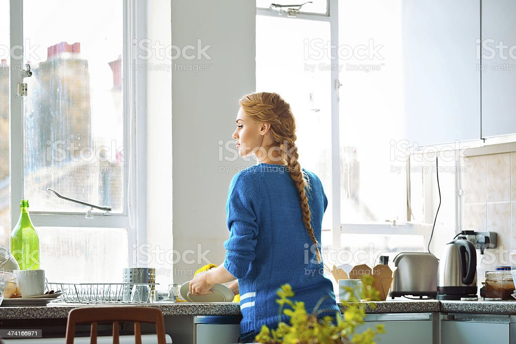 Woman washing dishes Young woman cleaning kitchen, washing dishes. 20-24 Years Stock Photo