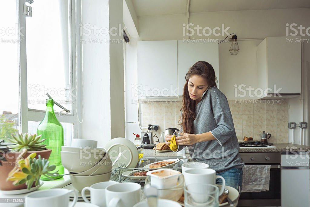 Woman washing dishes Young woman cleaning kitchen, washing dishes and talking on phone. 20-24 Years Stock Photo