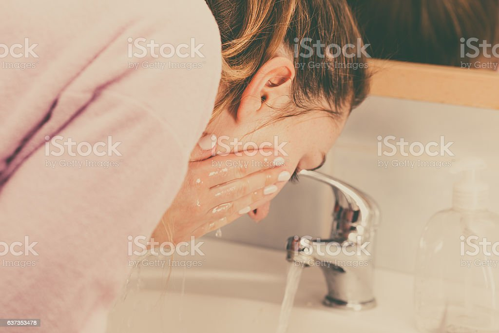Woman washing face in bathroom. Hygiene. stock photo