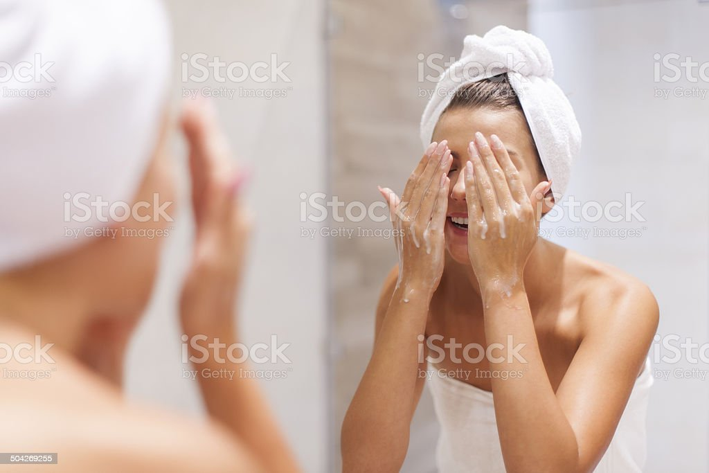 Woman washing face in bathroom stock photo