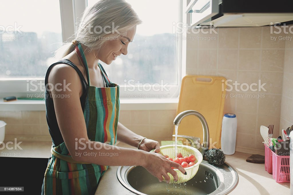 Woman washing fresh vegetables tomatoes in kitchen under water stream stock photo