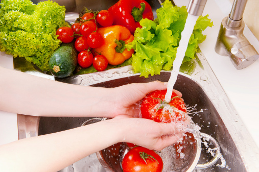 A woman washing fresh vegetables under the tap