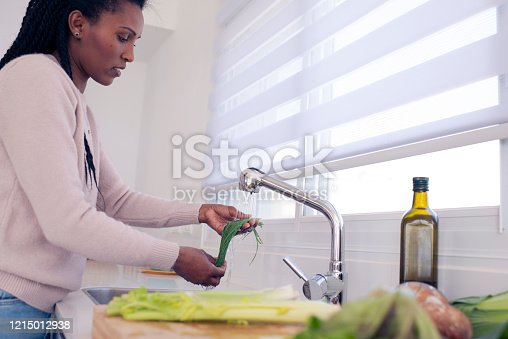 Close up young African woman washing scallion under faucet in the kitchen.