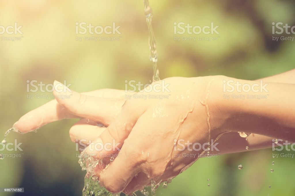 Woman washing hand outdoors. Natural drinking water in the palm. Young hands with water splash, selective focus stock photo