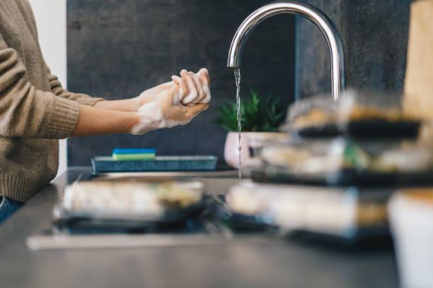 Frau wäscht Hände nach dem Auspacken zum Mitnehmen Essen – Foto