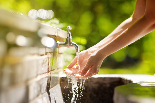 istock Woman washing hands in a city fountain in Rome, Italy 1080381158