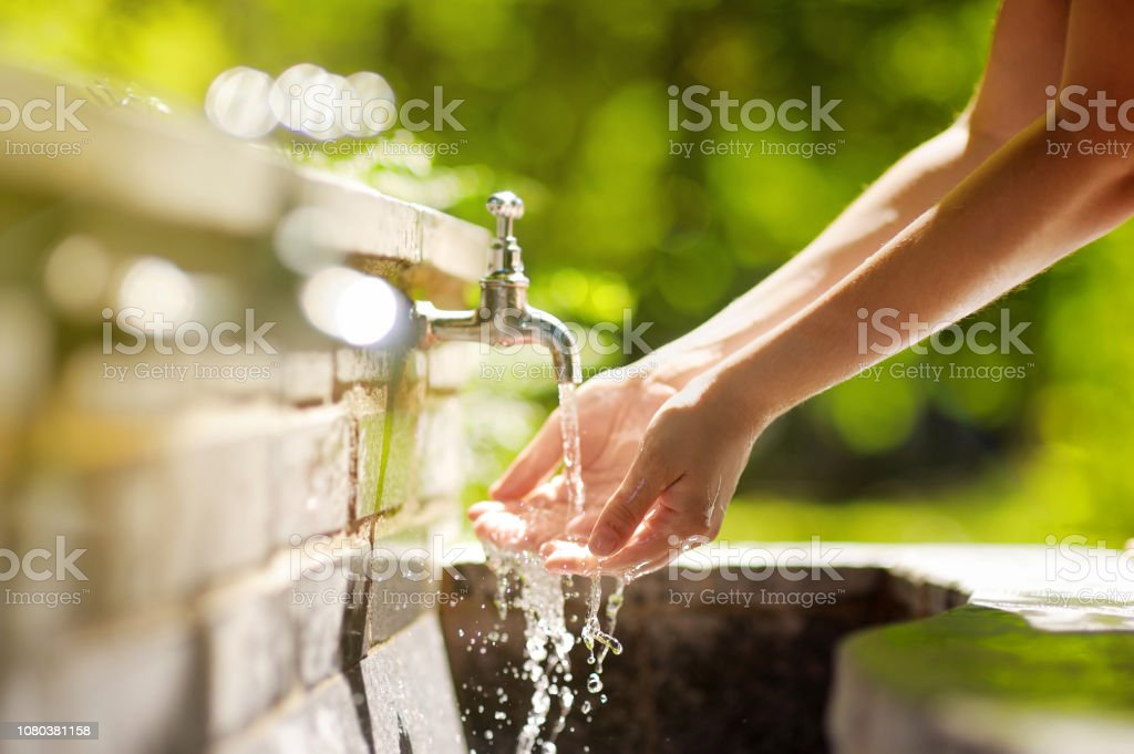Woman washing hands in a city fountain in Rome, Italy stock photo