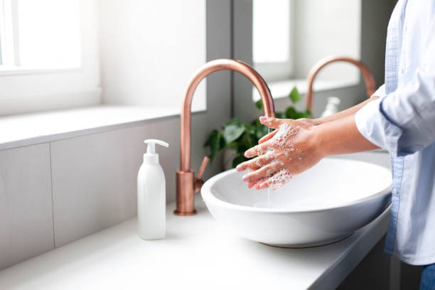 Woman washing hands under water tap. Self care and hygiene. Close up of female hand. stock photo