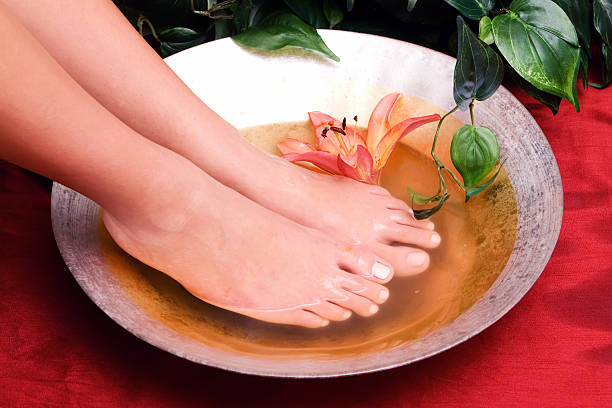 Woman washing her feet in bowl of water stock photo