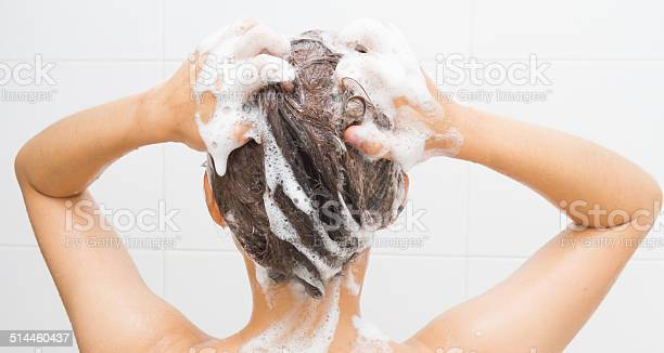 Woman washing her hair Woman washing her hair on white tiles background. Adult Stock Photo