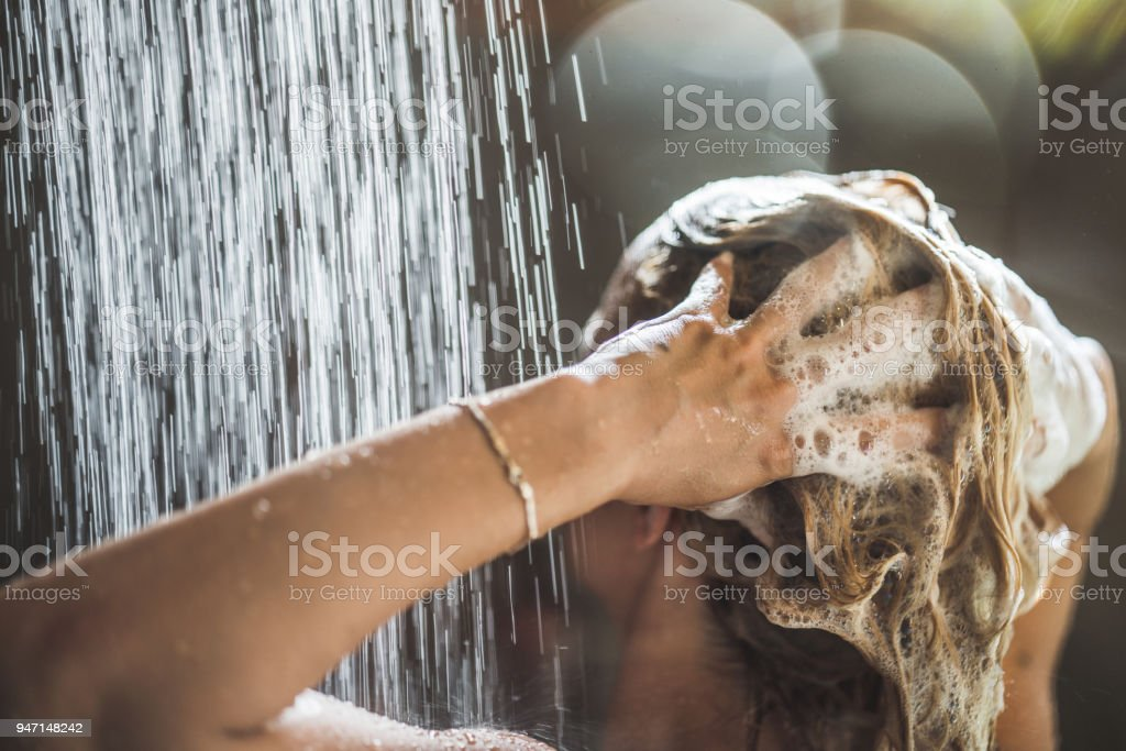 Woman washing her hair with shampoo under the shower. stock photo