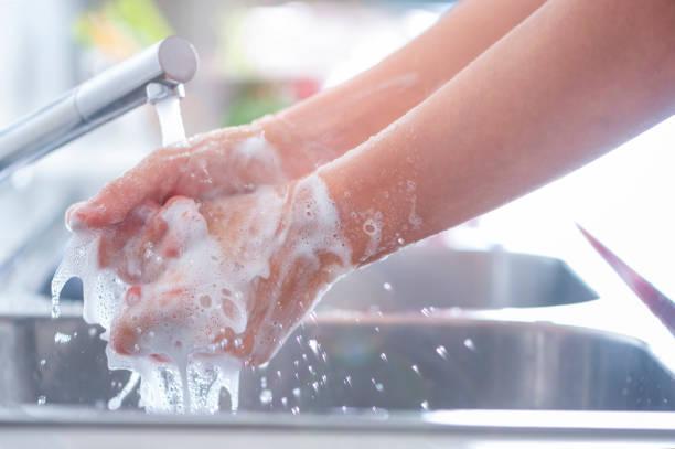 Frau wäscht ihre Hände an der Spüle. – Foto