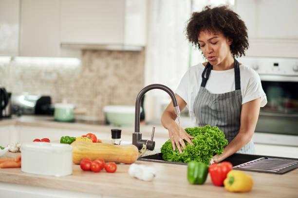 Frau waschen Salat in der Küche Waschbecken. – Foto