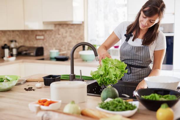 Frau waschen Salat im Waschbecken. – Foto