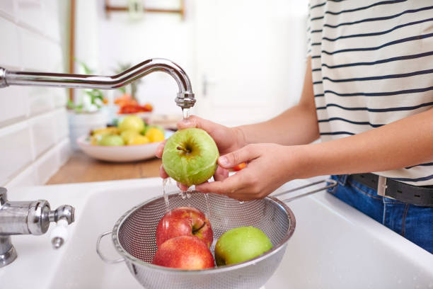 Woman washing seasonal fresh apples stock photo