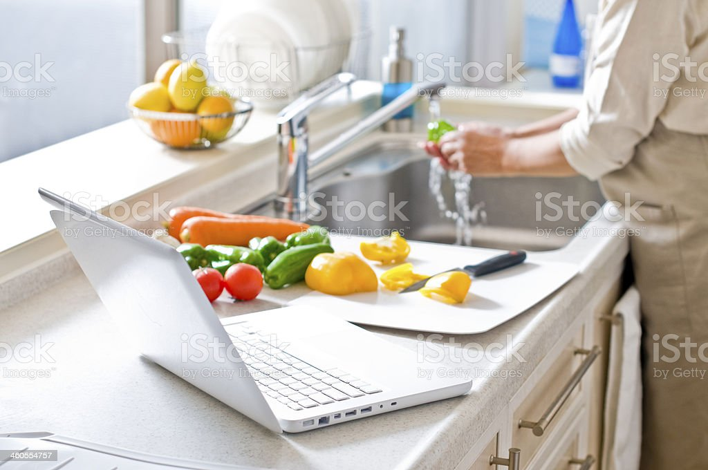 Woman washing vegetables next to an open laptop in a kitchen stock photo