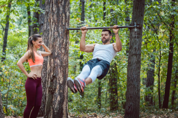 woman watches man doing exercises on high bars - horizontal bar stock photos and pictures