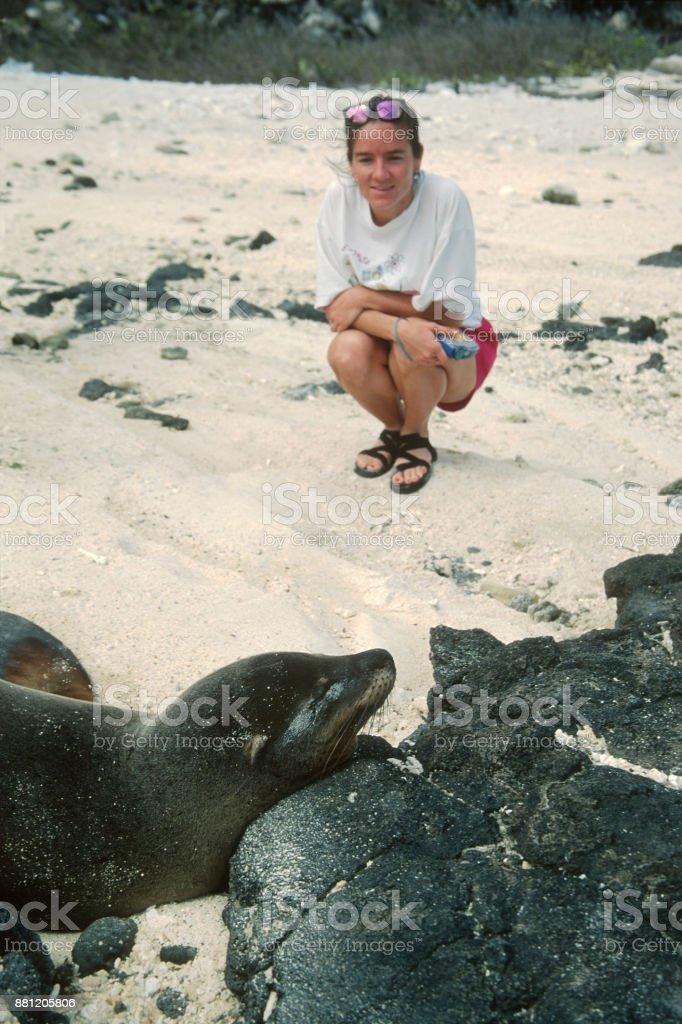 Woman watches sea lion Isla Santiago San Salvador Galapagos Islands Ecuador stock photo