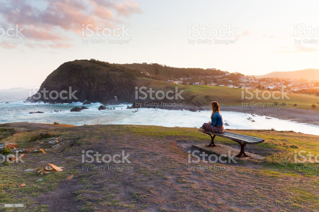 Woman Watches the Sun Set From a Wooden Bench stock photo