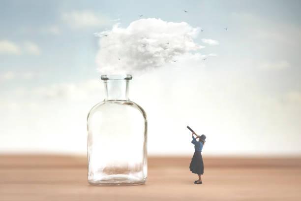 Frau beobachtet mit Teleskop eine Wolke, die von einer Vase befreit wird und in den Himmel entweicht – Foto