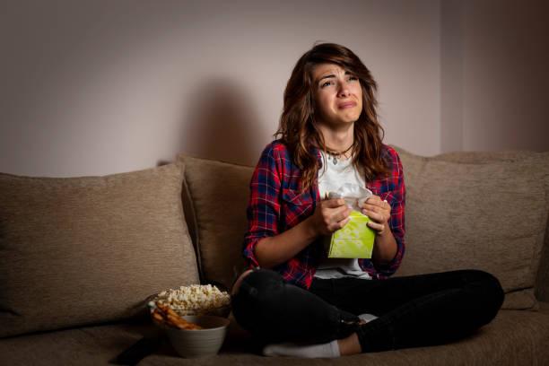Woman watching a drama movie and sobbing stock photo