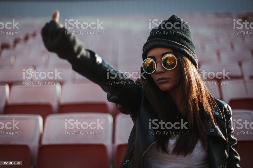 Woman watching a game and cheering outdoors stock photo
