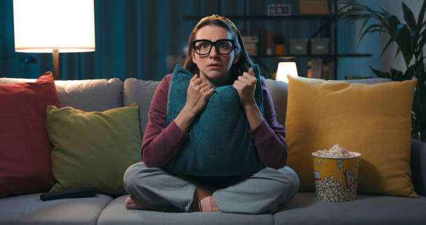 Woman watching a horror movie at home stock photo