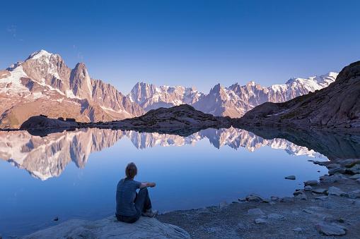 Woman watching Alps mountain range and beautiful reflection in lake