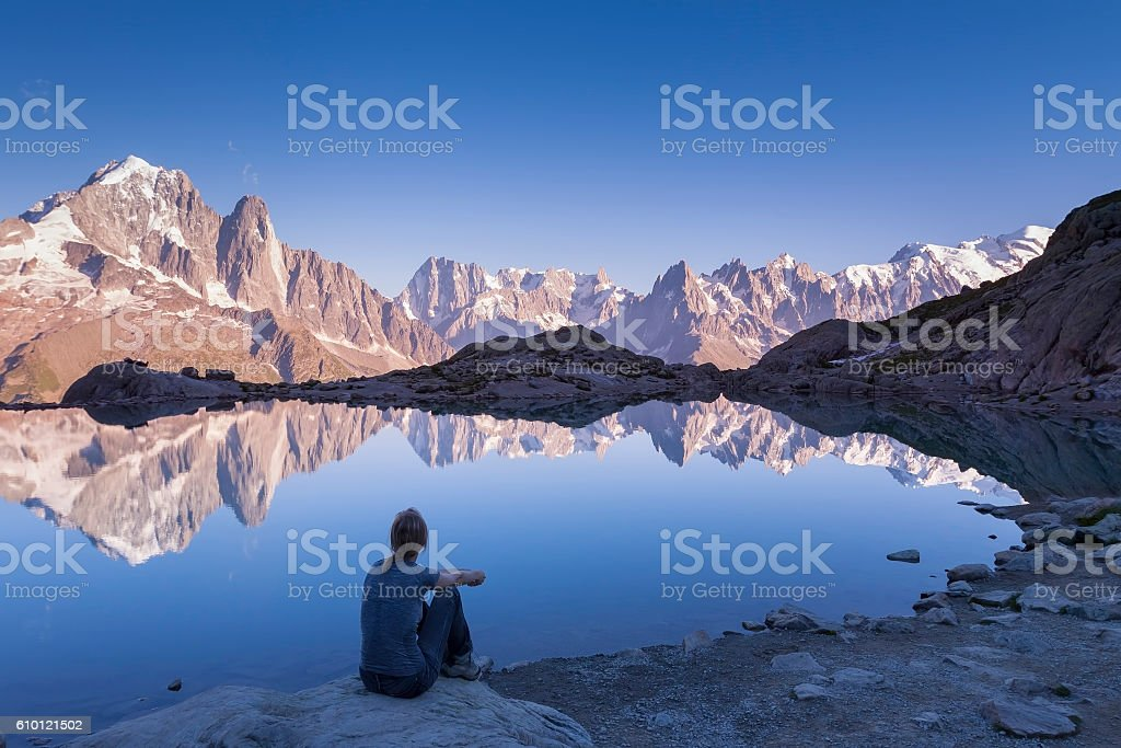 Woman watching Alps mountain range and beautiful reflection in lake stock photo