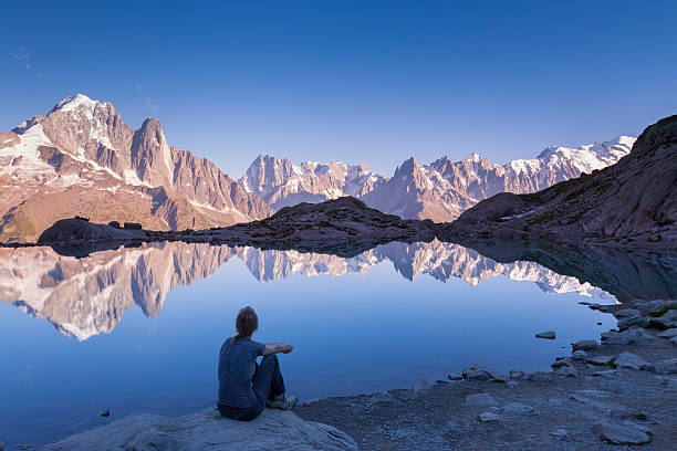 Woman watching Alps mountain range and beautiful reflection in lake - Photo