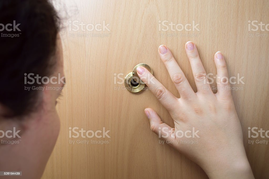 woman watching by the peep hole stock photo