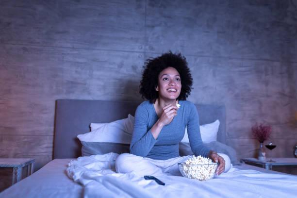 woman watching comedy on tv - watch imagens e fotografias de stock