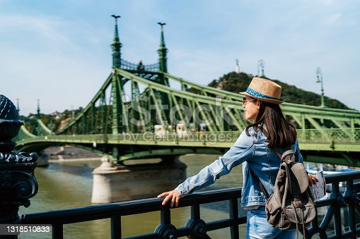 Young woman watching Danube river near  Liberty bridge in Budapest.