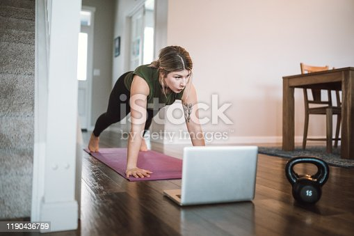 An adult woman does yoga and strength training exercises on a mat in her living room.  She follows an online exercise course video on her laptop.