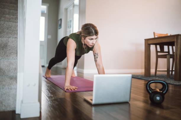 woman watching exercise tutorials online - dodatkowa praca zdjęcia i obrazy z banku zdjęć