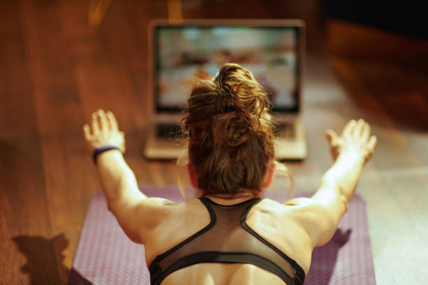 woman watching fit tutorial on internet while doing exercises stock photo