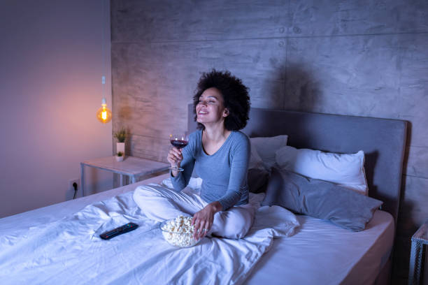 Woman watching funny movie on TV stock photo